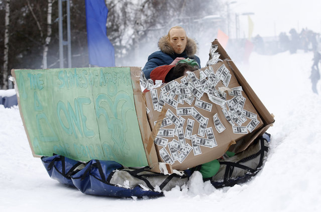 """A participant, wearing a mask depicting Russian President Vladimir Putin, competes during a contest on the longest distance and the most creative performance at the """"Battle sani"""" (Sledge battle) festival of self-made sledges in Moscow, Russia, February 23, 2016. (Photo by Maxim Zmeyev/Reuters)"""