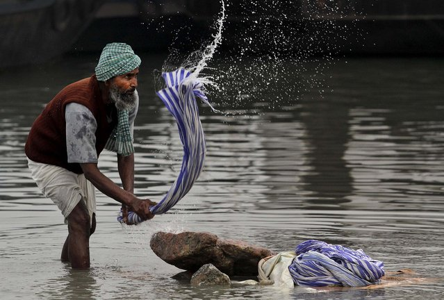 A Dhobi washes clothes in the River Brahmaputra on a cold winter morning in Gauhati, India, December 29, 2013. Dhobis are traditional laundry workers who wash clothes by hand and dry them in the sun, an occupation which has been in existence for generations. (Photo by Anupam Nath/Associated Press)
