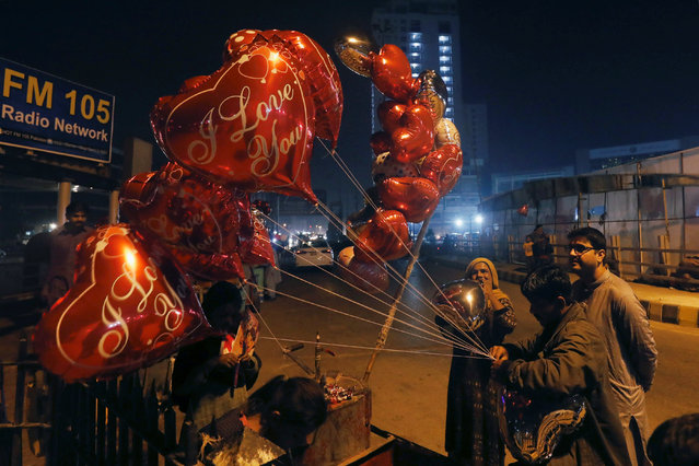 Imran ties as his wife inflates heart-shaped balloons for a customer on Valentine's Day from their cart along a road in Karachi, Pakistan on February 14, 2019. (Photo by Akhtar Soomro/Reuters)