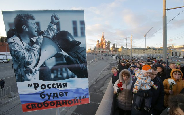 """People visit the site of the murder of Russian opposition politician Boris Nemtsov on the first anniversary of his death, with St. Basil's Cathedral seen in the background, in central Moscow, Russia, February 27, 2016. The placard reads """"Russia will be free!"""". (Photo by Maxim Shemetov/Reuters)"""