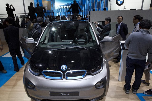 Attendees look at the latest car from BMW at the Shanghai Auto Show in Shanghai, Monday, April 20, 2015. (Photo by Ng Han Guan/AP Photo)