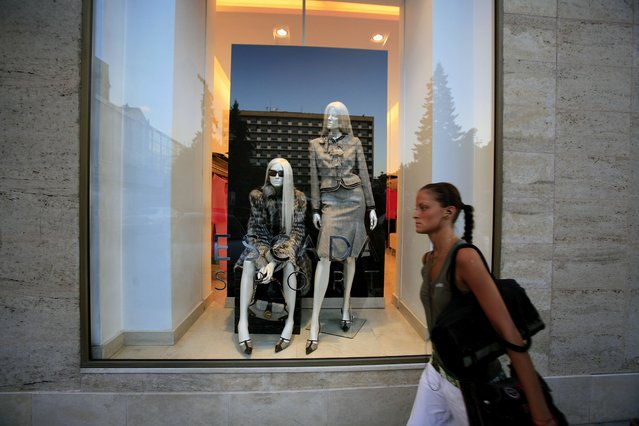 A woman walks past window in a luxury clothing store on September 5, 2006 Sofia, Bulgaria. (Photo by Christopher Furlong/Getty Images)