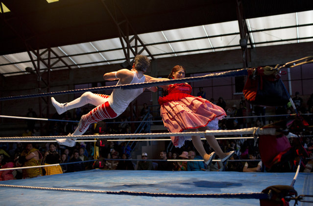Veteran cholita wrestler Jennifer Dos Caras, 45, competes in the ring with Randy Four in El Alto, Bolivia, January 21, 2019. The sport, known by the English-derived name catchascan, has delighted foreign tourists and photographers for years while building a sense of pride among indigenous women. (Photo by Juan Karita/AP Photo)