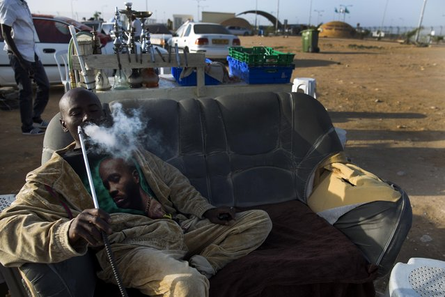 An African migrant smokes outside Holot detention center in the Negev Desert, southern Israel, Tuesday, April 21, 2015. Tens of thousands of African migrants have made their way to Israel in recent years. Most of these migrants came from Eritrea, an eastern African nation with one of the world's most dismal human rights records. (Photo by Tsafrir Abayov/AP Photo)