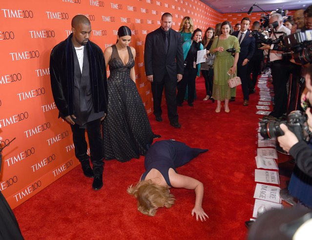 Honoree and Comedian Amy Schumer pretends to trip and fall on the floor  in front of honorees Kim Kardashian (2nd-L) and Kanye West (L) as they attend the Time 100 Gala celebrating the Time 100 issue of the Most Influential People at  The World at Jazz at Lincoln Center on April 21, 2015 in New York. (Photo by Timothy A. Clary/AFP Photo)