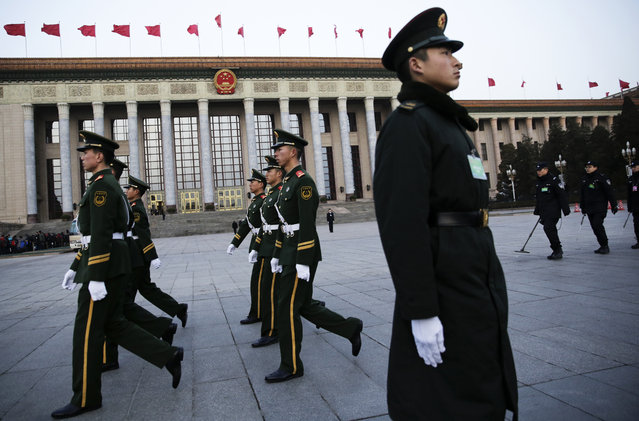 In this Saturday, March 5, 2016 photo, Chinese security personnel march past the Great Hall of the People where the opening session of the National People's Congress (NPC) is held in Beijing. (Photo by Mark Schiefelbein/AP Photo)