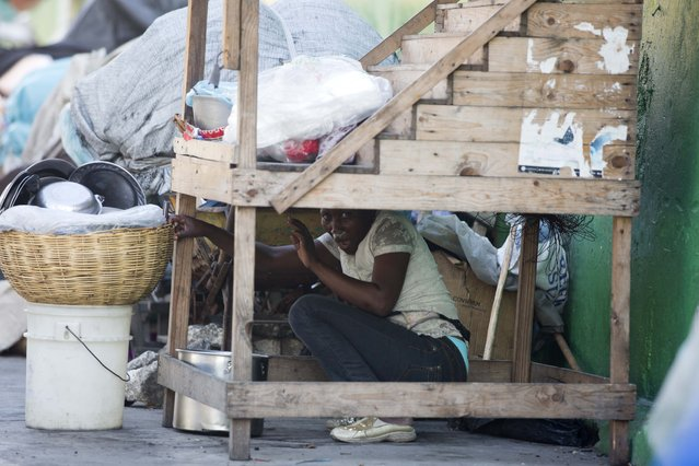 A street vendor hides during a clashes between protesters and national police officers as they demand the resignation of President Jovenel Moise and demanding to know how Petro Caribe funds have been used by the current and past administrations, in Port-au-Prince, Haiti, Saturday, February 9, 2019. (Photo by Dieu Nalio Chery/AP Photo)