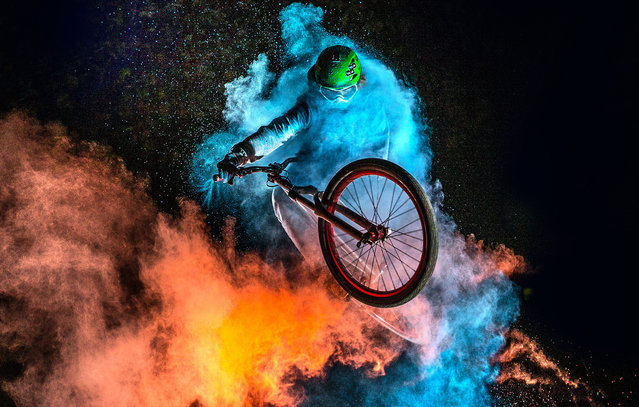 The biker with the holi powder behind whilst performing stunts. (Photo by Christoph Jorda/Caters News)