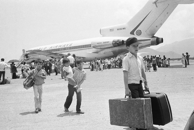South Vietnamese refugee deplane at Nha Trang airfield in Vietnam, Thursday, March 27, 1975 following a jet hop from Danang as a U.S. financed airlift, using civilian chartered jets, relocates thousands of former residents of Hue. (Photo by Nick Ut/AP Photo)
