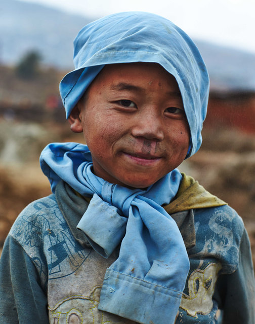 A dust covered young boy smiles for the camera during one of his long work days in Kathmandu Valley, Nepal, 18 January 2014. (Photo by Jan Moeller Hansen/Barcroft Images)