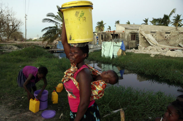 A woman carrying water and a baby on her back after collecting water in Beira, Mozambique, Monday, March 25, March 24, 2019. (Photo by Themba Hadebe/AP Photo)