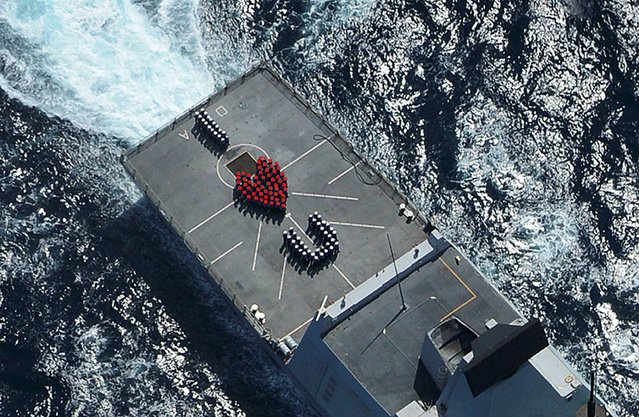 """Undated Ministry of Defence handout photo of the crew of the Royal Navy destroyer HMS Daring sending a Valentine's message to their loved ones back home by forming a red heart on the warship's flight deck. The message saying """"I Love You"""" was formed by sailors aboard the Type 45 destroyer heads back to its home base of Portsmouth, Hampshire, having spent nine months on deployment – one of the navy's longest missions. (Photo by Keith Morgan/MoD/Crown Copyright/PA Wire)"""