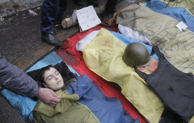 A protesters shows the face of a victim killed in clashes with police in Kiev's Independence Square, the epicenter of the country's current unrest, Thursday, February 20, 2014. (Photo by Efrem Lukatsky/AP Photo)