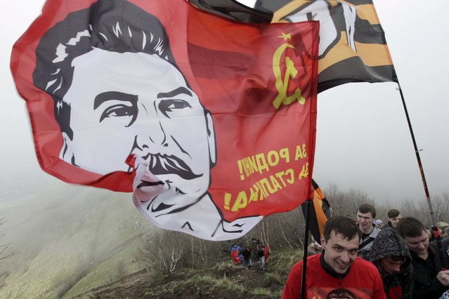 People climb up Mount Beshtau while holding a flag with an image of Soviet leader Joseph Stalin, near Zheleznovodsk in Stavropol region, Russia, May 3, 2015. The ascend of about two thousand participants was dedicated to the upcoming 70th anniversary of the victory over Nazi Germany in World War Two on May 9. (Photo by Eduard Korniyenko/Reuters)
