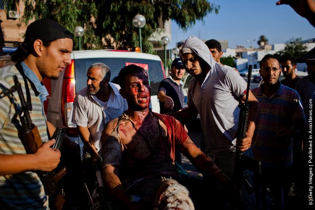 Libyan rebel fighters protect a pro-Gaddafi loyalist fighter from angry onlookers as he is brought in for medical attention to the Tripoli Central Hospital