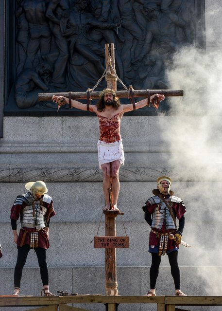 """Actor James Burke-Dunsmore stands on a crucifix whilst playing Jesus during The Wintershall's """"The Passion of Jesus"""" in front of crowds on Good Friday at Trafalgar Square on March 25, 2016 in London, England. (Photo by Chris Ratcliffe/Getty Images)"""