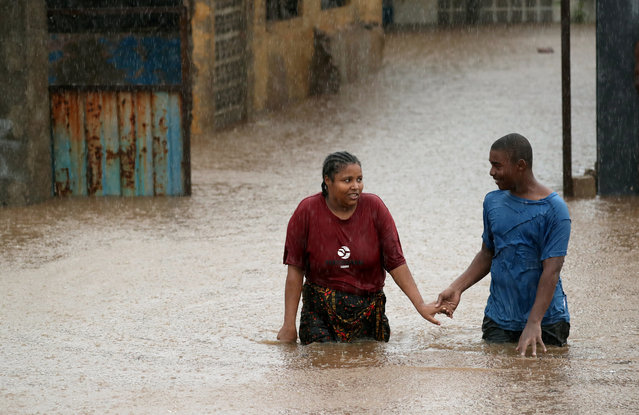 A man helps a woman through a flooded neighbourhood in the aftermath of Cyclone Kenneth, in Pemba, Mozambique, April 28, 2019. (Photo by Mike Hutchings/Reuters)