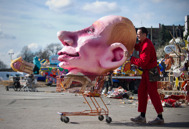 Float builder Jacques Tilly carries the head of a figure depicting Russian President Vladimir Putin in a shopping cart in Duesseldorf, Germany, 4 March 2014. The firgure was on display at the Rose Monday (Rosenmontag) Parade on 03 March with hundreds of thousands of visitors. (Photo by Jan-Philipp Strobel/EPA)