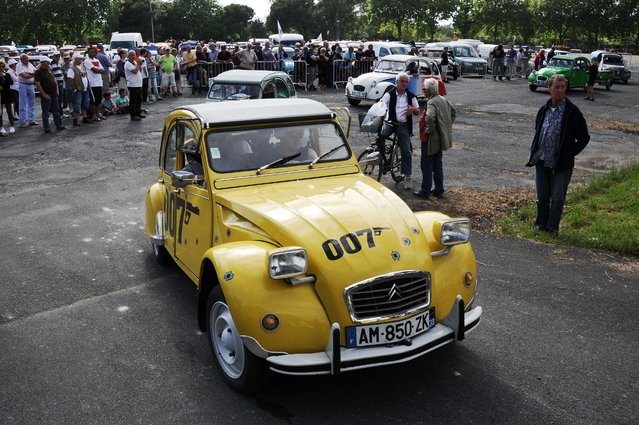 People arrive in their Cirtroen 2CVs during the 22nd National Meeting of French 2CV clubs in La Rochelle on May 13, 2015. (Photo by Xavier Leoty/AFP Photo)
