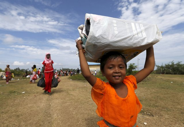 A Rohingya migrant child, who arrived in Indonesia by boat, carry belongings while walking to a bigger shelter inside a temporary compound for refugees in Kuala Cangkoi village in Lhoksukon, Indonesia's Aceh Province May 18, 2015. (Photo by Reuters/Beawiharta)