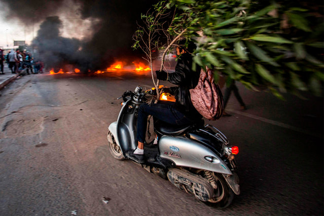 An Iraqi protester holds a broken tree as he drives a scooter towards other protesters blocking the road with a tire fire, during a demonstration against corruption and lack of services in the southern city of Basra on January 11, 2019. (Photo by Hussein Faleh/AFP Photo)