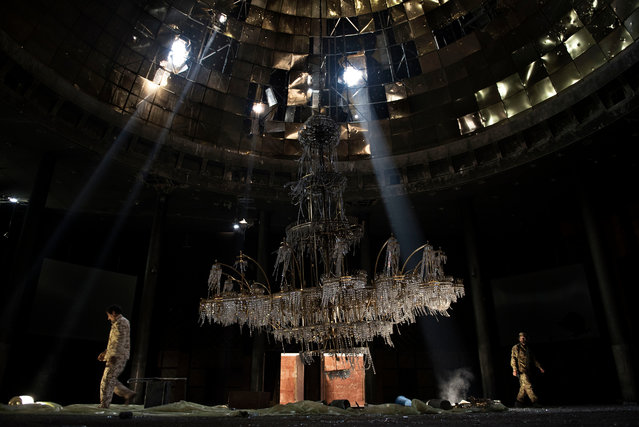"Current affairs and news category, professional shortlist. ""We are taking no prisoners"". Libyan forces affiliated to the Tripoli government walk around a huge chandelier at the Ouagadougou congress complex in Sirte, Libya. (Photo and caption by Alessio Romenzi/2017 Sony World Photography Awards)"