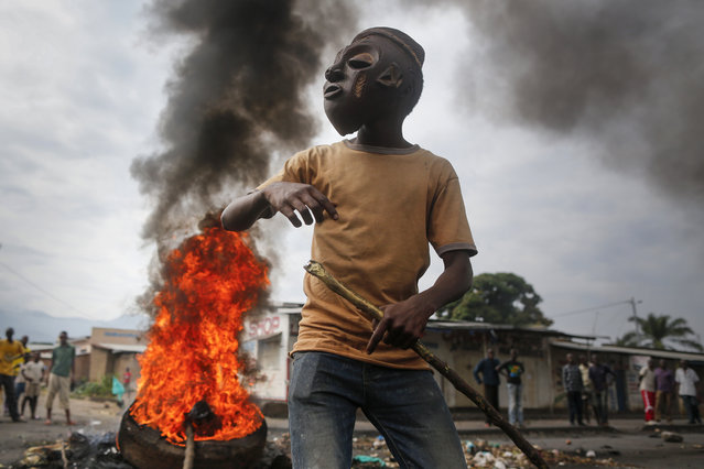 A masked Burundian protester faces soldiers in front of a burning barricade during an anti-government demonstration against President Pierre Nkurunziza's bid for a third term in the capital Bujumbura, Burundi, 25 May 2015. (Photo by Dai Kurokawa/EPA)