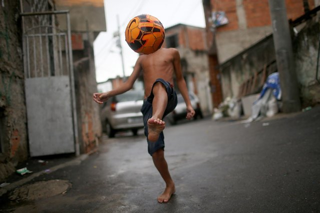 """A boy shows off his soccer skills in the Complexo do Alemao pacified """"favela"""" community in Rio de Janeiro, Brazil. (Photo by Mario Tama/Getty Images)"""