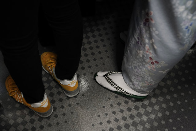 In this Wednesday, May 22, 2019, photo, a woman wearing a kimono stands next to a young woman wearing sneakers in a packed train traveling along the Yamanote Line in Tokyo. For most Tokyoites, the line means an incredibly punctual and efficient transportation system for commuting. For tourists, it offers a glimpse into the life of ordinary people living in the city. (Photo by Jae C. Hong/AP Photo)