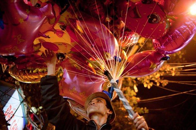 """Balloon vendor on the Hanoi old quarter street"". Balloon vendor wandered through the street maze of Hanoi old quarter at night. Photo location:  Hanoi, Vietnam. (Photo and caption by Sai Kit Leung/National Geographic Photo Contest)"