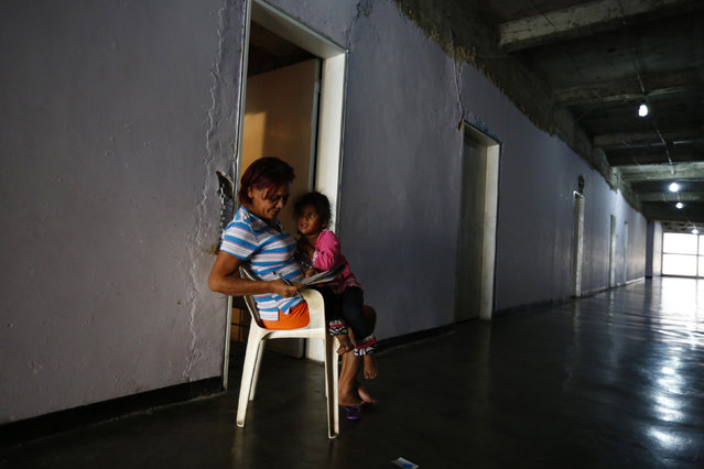 """Beatriz fills out a crossword while taking care of her grandchildren outside their apartment, inside of the """"Tower of David"""" skyscraper in Caracas February 3, 2014. (Photo by Jorge Silva/Reuters)"""