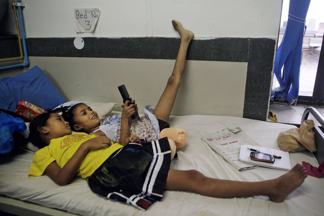 In this July 6, 2015, photo, Nepalese amputee victims and best of friends, Khendo Tamang, left, and Nirmala Pariyar, both 8, play on a mobile phone at the Bir Trauma Center in Kathmandu, Nepal. Each girl lost one leg in Nepal's massive April 25, 2015 earthquake that killed nearly 9,000 people dead and more than 22,000 injured. (Photo by Niranjan Shrestha/AP Photo)