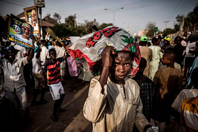 A boy cover himself with a plastic bag while All Progressives Congress Party (APC) supporters celebrate initial results released by the Nigerian Independent National Electoral Commission (INEC) in Kano, on February 25, 2019, two days after general elections. (Photo by Luis Tato/AFP Photo)