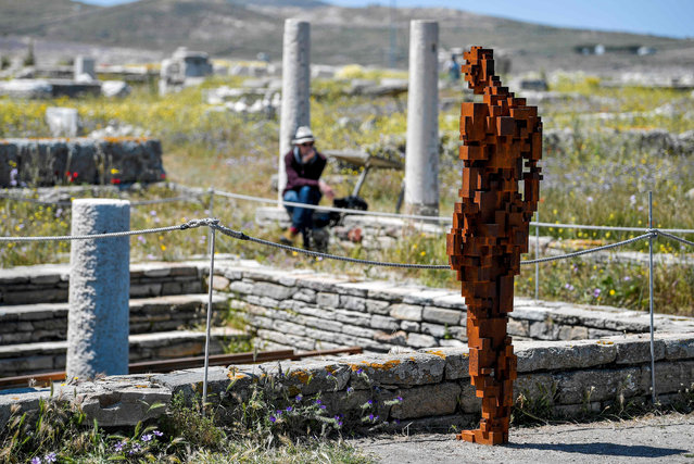 """A visitor sits next o the statue """"Water"""" by renowned British artist Antony Gormley, part of his exhibition """"Sight"""" at the archeological site of the island of Delos, a UNESCO World Heritage Site on May 3, 2019. Near the Greek island of Mykonos, in the Cyclades, the uninhabited island of Delos, known for its archaeological riches, hosts for the first time on an ancient Greek site an exhibition of contemporary art: 29 sculptures by the British artist Antony Gormley. The exhibition will run until October 30, 2019. (Photo by Louisa Gouliamaki/AFP Photo)"""