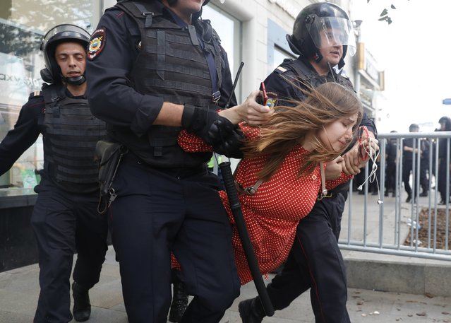Police officers detain a woman during an unsanctioned rally in the center of Moscow, Russia, Saturday, July 27, 2019. Russian police are wrestling with demonstrators and have arrested hundreds in central Moscow during a protest demanding that opposition candidates be allowed to run for the Moscow city council. (Photo by Pavel Golovkin/AP Photo)