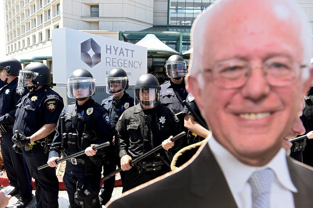Police form a scrimmage line behind a picture of Democratic presidential candidate Sen. Bernie Sanders outside the California Republican Party convention in Burlingame, California April 29, 2016. (Photo by Noah Berger/Reuters)