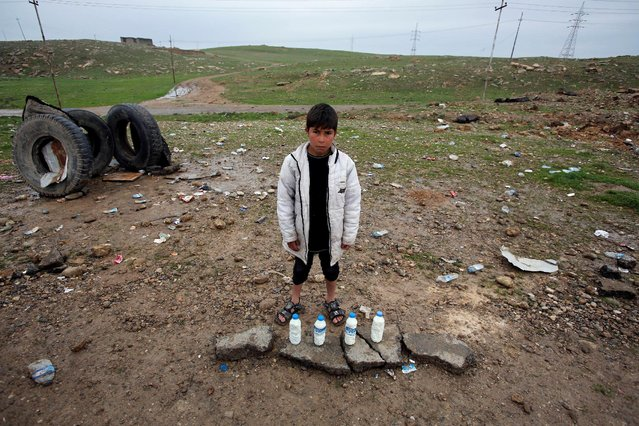 A boy sells milk on the street near the city of Mosul, Iraq March 18, 2017. (Photo by Youssef Boudlal/Reuters)