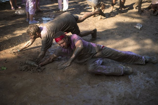 Revellers dive in the mud during the Batalla de Vino (Wine Battle) in Haro, northern Spain June 29, 2015. (Photo by Vincent West/Reuters)