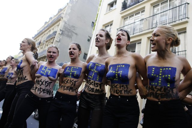 """Topless activists of the Ukrainian women movement Femen take part in a """"Fascist's epidemic"""" action, on April 22, 2014 in Paris, to disturb a press conference of French far-right National Front (FN) party, marking the start of the FN's electoral campaign for the European elections. The European Parliamentary elections will take place from May 22 to May 25, 2014. (Photo by Thomas Samson/AFP Photo)"""