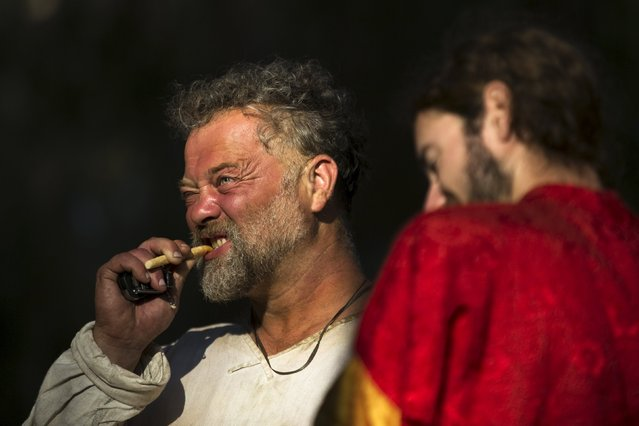 An enthusiast wearing a costume cleans his teeth during a re-enactment of a decisive Crusaders battle in northern Israel's Galilee region July 4, 2015. (Photo by Amir Cohen/Reuters)