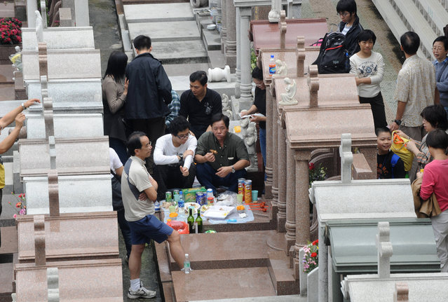 "A family has lunch at a cemetery during the public holiday of ""Ching Ming"" in Hong Kong on April 4, 2008.  The Qingming or Ching Ming Festival, which falls on the 104th day after the winter solstice, is also known as All Souls Day where people pay their respects to past ancestors by cleaning their graves, present offerings of food, and burning joss paper. (Photo by Mike Clarke/AFP Photo)"
