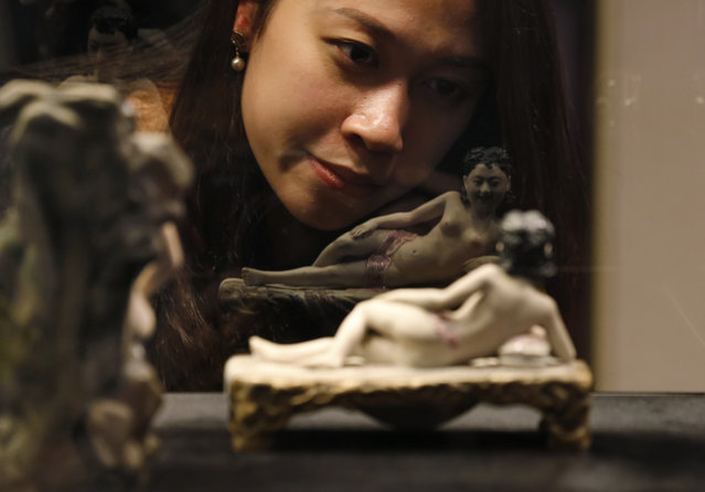 "A woman looks at an erotic figure during a preview of an exhibition ""Gardens of Pleasure: s*x In Ancient China"" presented by the Sotheby's Hong Kong Gallery in Hong Kong Tuesday, April 15, 2014. The exhibition features more than 100 pieces of ancient Chinese erotic art from the Ferdinand M. Bertholet Collection, with objects dating from the Chinese Han Dynasty to the Qing Dynasty. (Photo by Kin Cheung/AP Photo)"