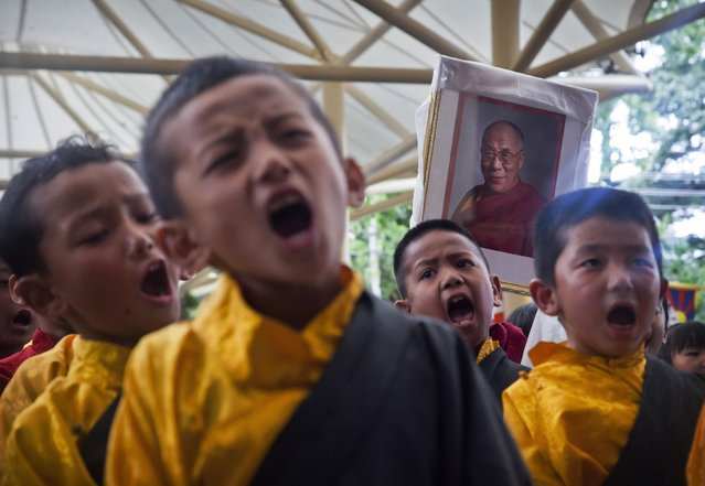 Exiled Tibetan school children wearing traditional costumes carry a portrait of the Dalai Lama as they sing at a gathering to celebrate their spiritual leader's 80th birthday in Dharmsala, India, Monday, July 6, 2015. (Photo by Ashwini Bhatia/AP Photo)