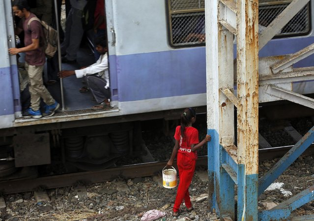 An Indian girl holds a can filled with water and waits for a train to pass as she walks to defecate in the open in Mumbai, India, Tuesday, June 30, 2015. Toilets are taken for granted in the industrialized West, but still are a luxury for a third of the world's people who have no access to them, according to a report by the World Health Organization and UNICEF released Tuesday. (Photo by Rajanish Kakade/AP Photo)