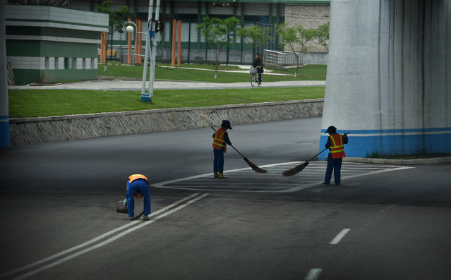 Women clean the streets with twig brooms in Pyongyang, North Korea on May 5, 2016. (Photo by Linda Davidson/The Washington Post)