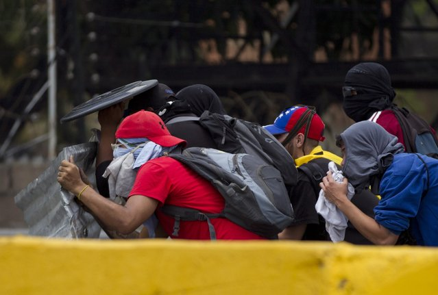 Demonstrators clash with the Bolivarian National Guard during a protest in Caracas, Venezuela, Monday, April 10, 2017. (Photo by Ariana Cubillos/AP Photo)