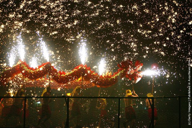 Athletes perform Dragon Dance in fireworks during a new year celebration at Beijing Happy Valley