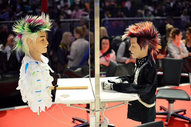 """Two dolls styled by participants await judging during the contest """"Day style"""" of the OMC Hairworld World Cup on May 4, 2014 in Frankfurt am Main, Germany. (Photo by Thomas Lohnes/Getty Images)"""