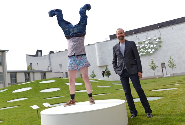 "Austrian artist Erwin Wurm (R) stands next to an extra of his participation sculpture ""Hose lueften, Haende hoch"" (air out pants, hands high) at the garden of the Staedel Museum, in Frankfurt am Main, Germany, 06 May 2014. The series ""Wurm: One Minute Sculptures"" include painted or written instructions tell the person what they have to do and where for 60 seconds. The exhibition runs from 07 May to 13 July. (Photo by Arne Dedert/EPA)"