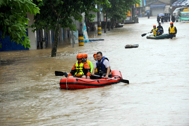 Rescuers use inflatable boats to evacuate residents from a neighborhood flooded by heavy rains from Typhoon Chan-Hom in Shaoxing in eastern China's Zhejiang province Saturday, July 11, 2015. (Photo by Chinatopix via AP Photo)